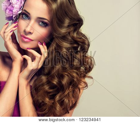 Beautiful girl with long wavy hair.  Brunette  model with curly hairstyle with pink flower in her hair. Cosmetics, makeup and manicure nails.