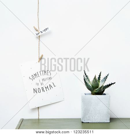 Mock up. Simple garland poster with quote I PRETEND TO BE NORMAL and succulent growing on concrete pot. Hipster scandinavian home interior decoration.