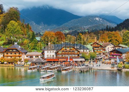 Schonau am Konigssee Germany - October 17 2015: A sightseeing boat cruising on Konigssee ( King's Lake ) surrounded by colorful autumn trees and boathouses on a sunny morning~ Beautiful scenery of Bavarian countryside in Berchtesgaden Germany.