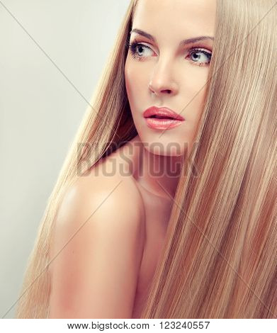 Beautiful blonde woman with long  straight  healthy and shiny hair.  Hair care .