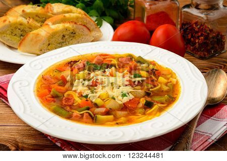 Minestrone- italian soup with vegetables on brown wooden table.