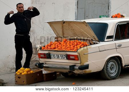 BAKU, AZERBAIJAN - DECEMBER 22 2013  Man stretching next to car with oranges for sale in boot. A fruit seller bring produce from the countryside into Baku, the capital city of Azerbaijan.