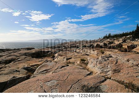 Walking along the rocky shore of Maine on a clear and sunny summer day.