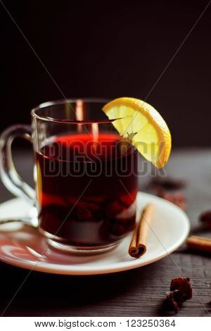 A Cup of hibiscus tea from Sudanese rose with lemon and cinnamon sticks on a black wooden background