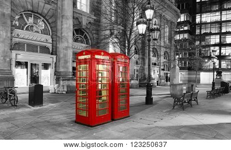 Red telephone booth in the City of London by night