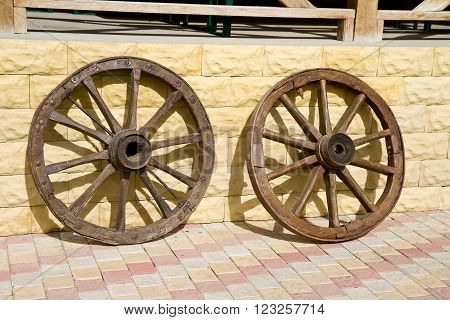 Wooden wheels of old carts hung on a wall.