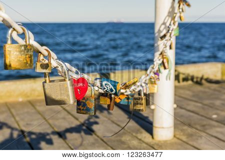 Red padlock in the shape of a heart on a chain on the pier.