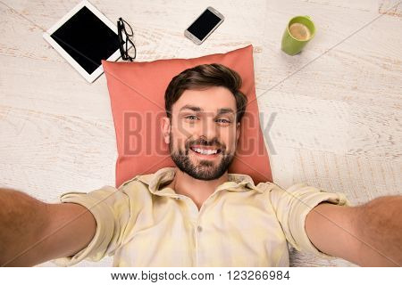 Attractive Man With Stubble Making Selfie Lying On Floor