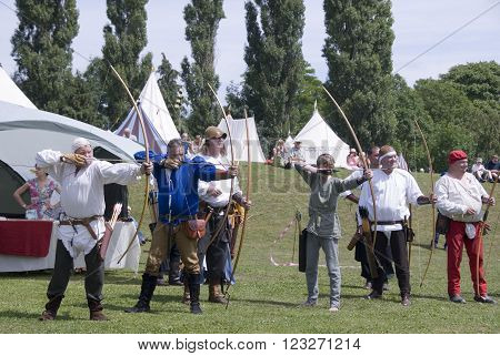 TEWKESBURY, GLOC. UK- JULY 11: Re-enactors in costume compete in longbow archery competition on 11 July 2014 at Tewkesbury Medieval Festival