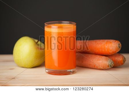 Food. Fruits and vegetables. An apple some carrots and a glass of fresh juice on the wooden table dark background