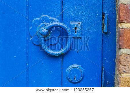A metal blue painted latch on a blue painted wooden door