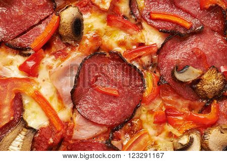 Close-up pepperoni pizza fragment as a background texture