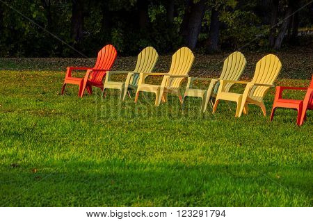 Row of lawn chairs on a green grass background in summer time