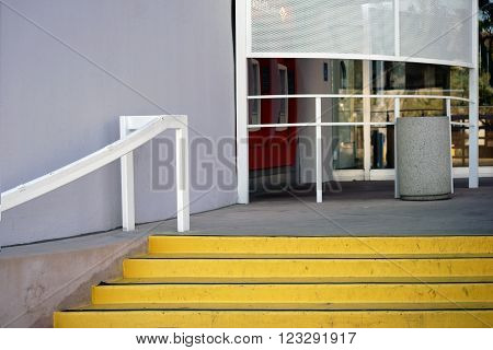 A bank entrance with a staircase and ATMs near the entrance door.