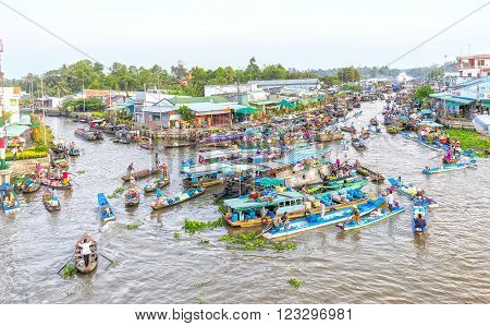 Soc Trang, Vietnam - February 3rd, 2016: Agricultural morning floating market bustling with agricultural boatload focus rotation trafficking intersection into river in sunny morning as wetland culture in Soc Trang, Vietnam