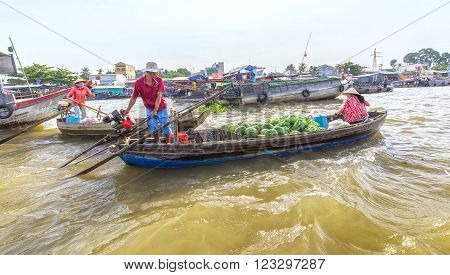 Can Tho, Vietnam - February 4th, 2016: Couple carrying farm produce trade on river with boats loaded with watermelon, cabbages, moving in floating market sales method wetland in Can Tho, Vietnam