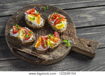 Tomato and cheese bruschetta on a rustic wooden cutting board. Healthy breakfast snack or appetizer with wine