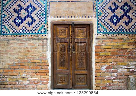 old carved wooden double doors with mosaic on the walls the Central Asian style Registan square Samarkand Uzbekistan