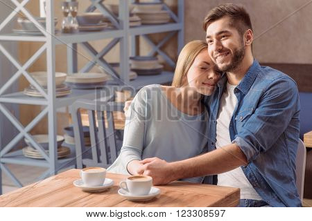 My protection. Pleasant romantic young couple sitting at the table and bonding to each other while resting in the cafe