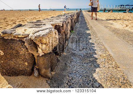 Waikiki, Honolulu, Hawaii, USA - December 13, 2015: Pathway to the jetty of the Atlantis Submarines Waikiki. On Waikiki Beach, near Fort DeRussy Broadwalk. A stone wall can be seen holding up the beach sand.