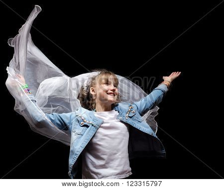 Girl teenager in a jeans jacket and flying veil. The concept of early marriage, dreams of a wedding.
