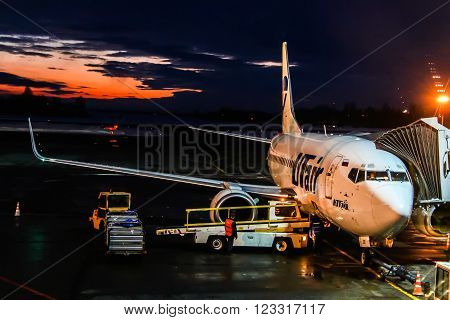 UFA RUSSIA - FEBRUARY 18 2016: UTair Boeing 737 is boarded in the Ufa International Airport at the background of the sunset.