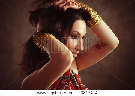 Indian woman with gold bracelets and mehndi on hands. Traditional mehndi on  Indian woman hands. Ethnic henna mehndi on Indian girl.