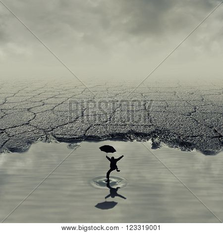 Surrealistic image with a boy jumping in a pothole of cracked asphalt. Broken pavement with a dirty water puddle.