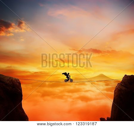 Boy with angel wings balance on a rope over a chasm riding a bicycle.Self overcoming and risk taking concept. Beautiful sunset background over the clouds