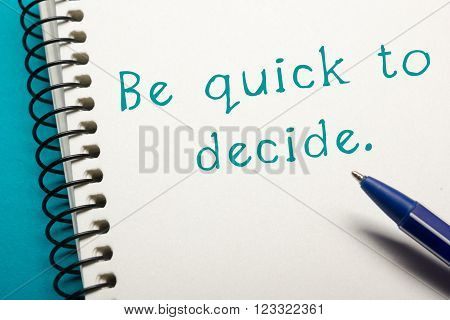 Be quick to decide - Office table top view. Notepad with text and pen . poster