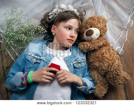 Girl teenager treats wedding accessories. Girl lying on the floor. In the picture, wedding veil, a teddy bear, a box for an engagement ring