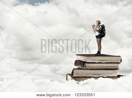 Young woman hiker standing on pile of books