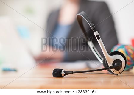 Close up of headset on the desk. Young female operator is sitting and using laptop on background