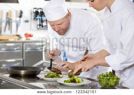 Cheerful chef prepares meat dish in a professional kitchen at restaurant or hotel. Team work.