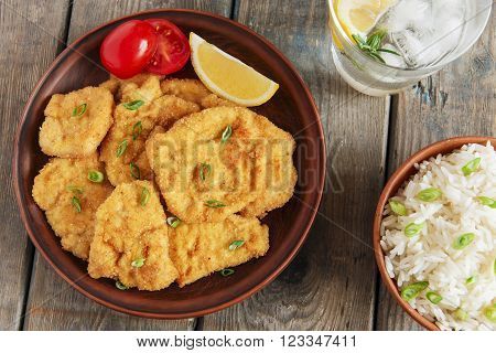 roasted schnitzel chop escalope with lemon, tomato and rice.