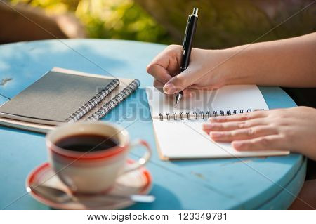 Woman right hand writing journal on small notebook at outdoor area in cafe with morning scene