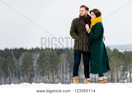 the beautiful loving couple walks in the winter outdoors