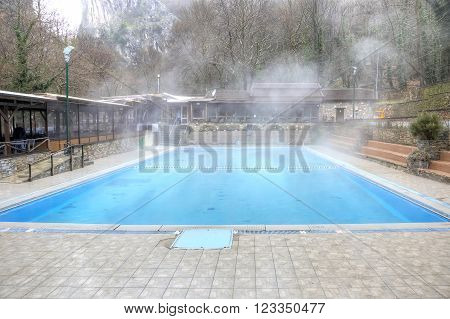 LOUTRA POZAR ARIADAEUS, GREECE -  March 15, 2016: People swim in a pool of hot water from the thermal spring.
