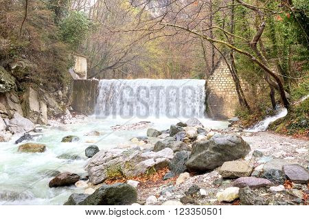 Termopotamos River. Cascade of artificial waterfalls on the mountain Voras by the thermal source