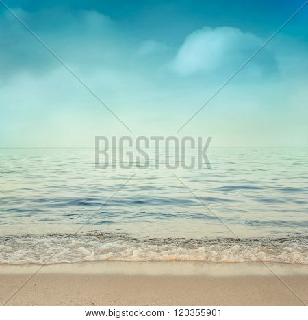 Sea summer abstract background. Golden sand beach with blue ocean and cloudscape and sunset in the back. Summer. Golden sand