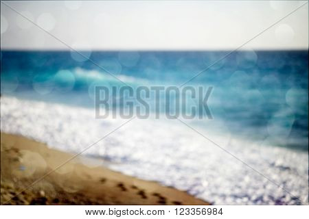 background of blurred beach and sea waves with bokeh lights, sandy beach with turquoise water, bright white sun lights bokeh, travel and summer holidays concept, vintage and retro effect