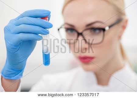 Cheerful female researcher is making experiments in laboratory. The woman is holding a flask of blue liquid and looking at it with concentration. Focus on glass tube