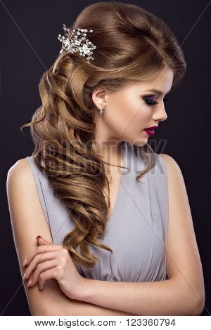 Beautiful girl with perfect skin, evening make-up, wedding hairstyle and accessories.Beauty face. Picture taken in the studio. Hairstyle Rear View