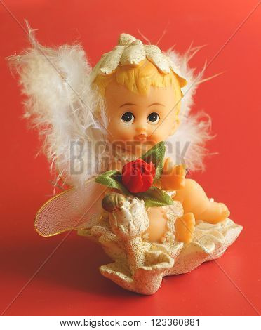 Little toy statue of fluff angel on red background