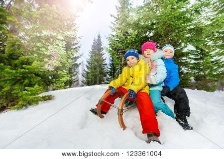 Group of little boys and girls in colorful clothes on the sledge slide down the slope