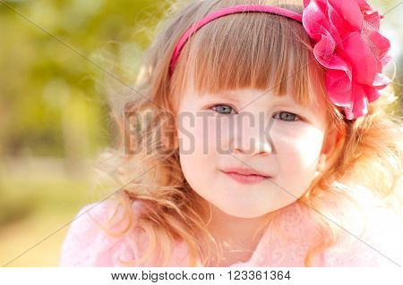 Smiling kid girl 3-4 year old wearing floral hairband outdoors. Looking at camera. Childhood.