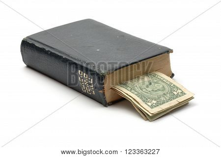 Old Hebrew bible book with dollar notes as bookmark. Isolated on white