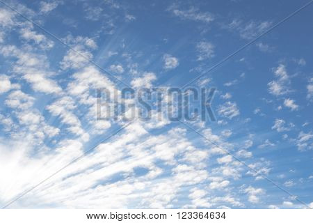 Deep blue summer sky with small Altocumulus clouds and bright sunrays sunbeams
