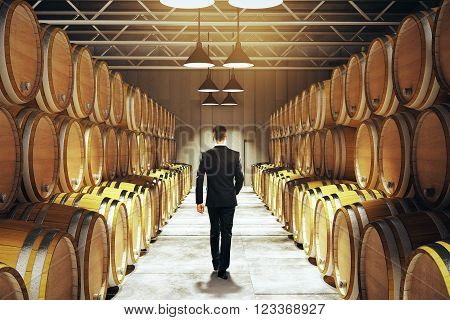 Caucasian businessman walking between barrel stacks in winery. 3D Render