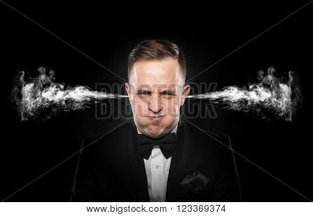 Stressful man with smoke or fume coming out from his ears on dark background.